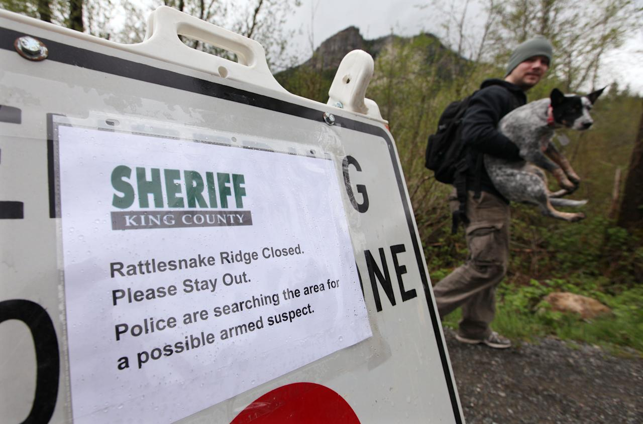 A hiker carries his dog past a sign advising of a closed trail just miles from where a gun-toting survivalist is suspected of killing his wife and daughter several days earlier Friday, April 27, 2012, in North Bend, Wash. Peter Alex Keller may be holed up in a self-made fort not far from where Seattle's outer suburbs give way to the vast recreational playground of Cascade Mountains. Police expect more people to hit the nearby trails this weekend, and deputies are warning them to steer clear of Keller if they think they see him. (AP Photo/Elaine Thompson)