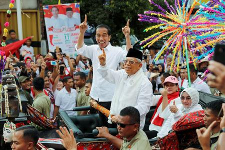 FILE PHOTO: Indonesia's President and presidential candidate for the next election Joko Widodo and his running mate for the upcoming election Ma'ruf Amin gesture as they greet their supporters at a carnival during campaign rally in Tangerang, Banten province, Indonesia, April 7, 2019. REUTERS/Willy Kurniawan/File Photo