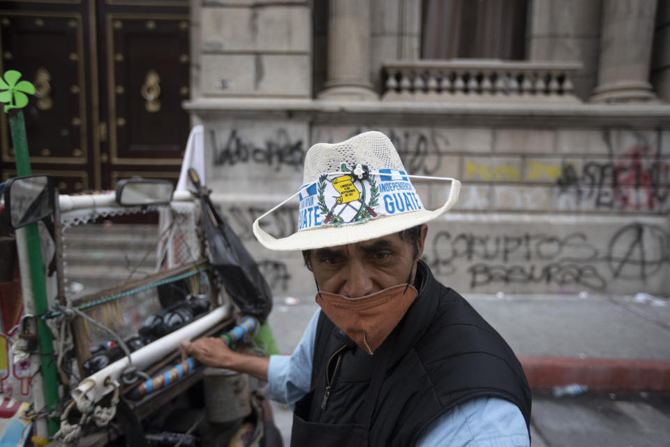 Ice creme vendor Manuel Sosa walks in front of the Congress building area that was damaged during protests in Guatemala City, Sunday, Nov. 22, 2020. Protesters broke into the building and set it partially on fire amid growing demonstrations against President Alejandro Giammattei and the legislature for approving a controversial budget that cut educational and health spending. (AP Photo/Moises Castillo)