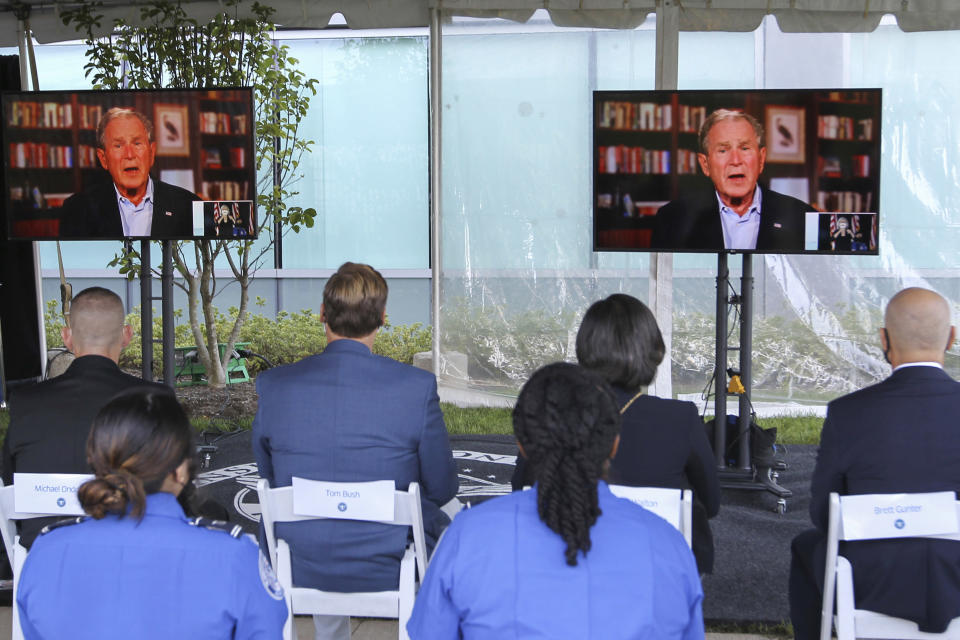 Screens display a video of former President George W. Bush speaking during an event to commemorate the 20th anniversary of the Sept. 11, 2001, terrorist attacks, Saturday, Sept. 11, 2021, in Springfield, Va. (AP Photo/Luis M. Alvarez)