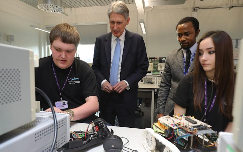 Philip Hammond chats to staff and students at the Advanced Engineering Centre at Dudley College during a visit to the West Midlands today - 2017 Getty Images