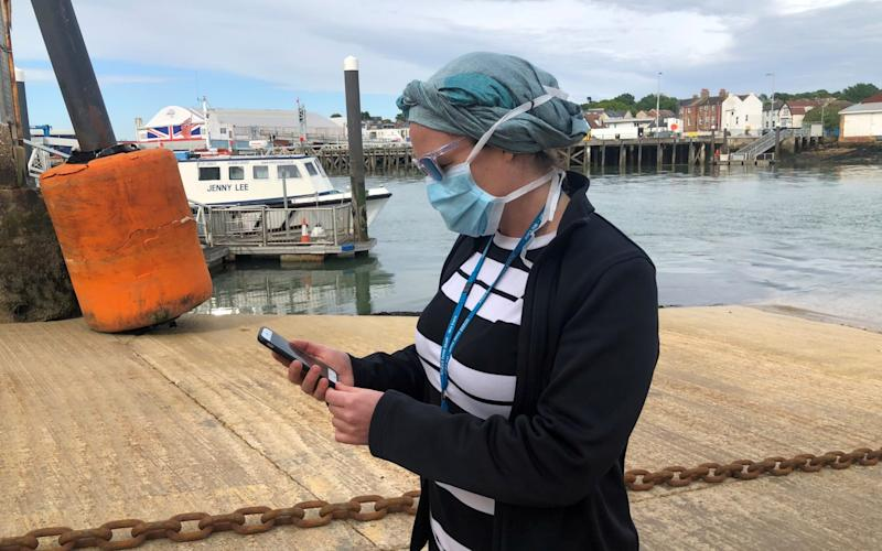 UK National Health Service employee Anni Adams looks at new NHS app to trace contacts with people potentially infected with the coronavirus disease (COVID-19) being trialled on Isle of Wight, Britain, May 5, 2020 - Reuters