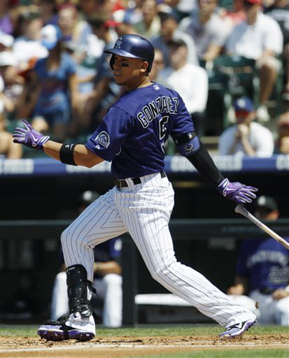 Colorado Rockies' Carlos Gonzalez follows the flight of his RBI-single against the Chicago Cubs in the first inning of a baseball game in Denver, Sunday, July 21, 2013. (AP Photo/David Zalubowski)