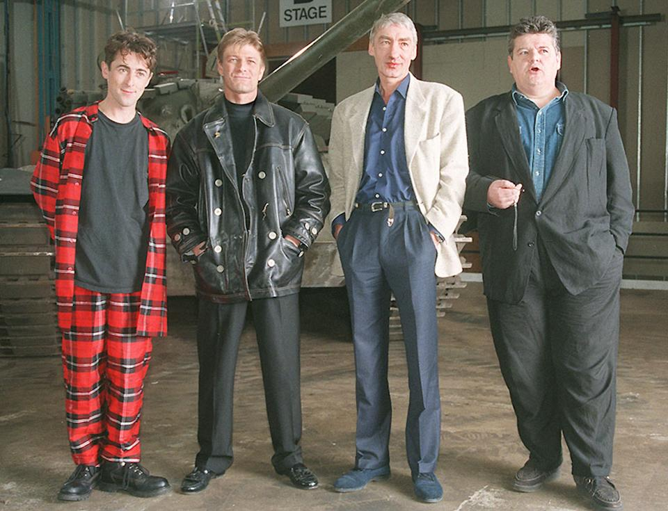 """PAP 8 22.1.95. LEAVESDEN. Villians of  the new James Bond film """"Goldeneye"""" , line up infront of a tank,  during a photocall at Leavesden Airfield, Herts, today (Sunday). L/R, Alan Cumming who is Boris,  Sean Bean who plays rouge agent 006, Alec Trevelyan,  Gottfried John who is Ourumov and Robbie  Coltrane who plays Valentin. Christmas 1995 is the projected world-wide release date for the   40 million thriller.  See PA story SHOWBIZ Bond. PA News, Stefan Rousseau. /PJ.   (Photo by PA Images via Getty Images)"""