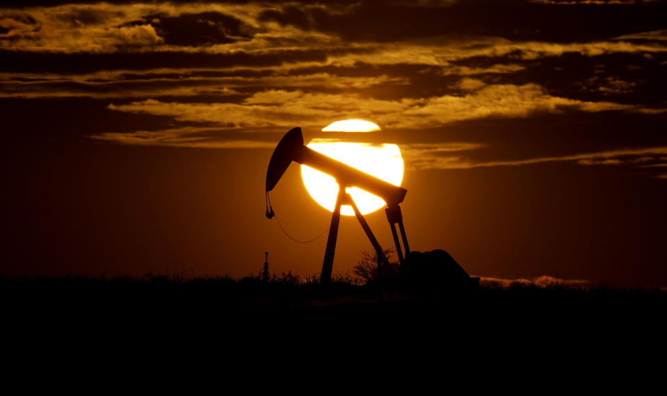 FILE - In this Wednesday, April 8, 2020, file photo, the sun sets behind an idle pump jack near Karnes City, Texas. In 2020, the coronavirus pandemic created winners and losers in the business world. The oil industry was pummeled after travel was halted in efforts to contain the coronavirus, sending demand for jet fuel and gasoline plummeting. (AP Photo/Eric Gay, File)