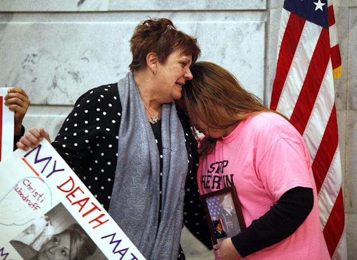 Jenni Woodruff (left), weeps as she clutches a poster with her daughter Christi's photograph. This was in Frankfort, Kentucky, where she was trying to convince legislators to approve needle exchange.