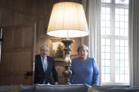 British Prime Minister Boris Johnson, left, and Chancellor of Germany, Angela Merkel pose for photographers before their bilateral meeting at Chequers, the country house of the Prime Minister of the United Kingdom, in Buckinghamshire, England, Friday July 2, 2021. Johnson is likely to push Angela Merkel to drop her efforts to impose COVID-19 restrictions on British travelers as the German chancellor makes her final visit to Britain before stepping down in the coming months. Johnson will hold talks with Merkel at his country residence on Friday. (Stefan Rousseau/Pool Photo via AP)