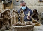 A Palestinian carpenter carves religious statues and figurines from olive wood at a shop near the Church of the Nativity in the West Bank city of Bethlehem