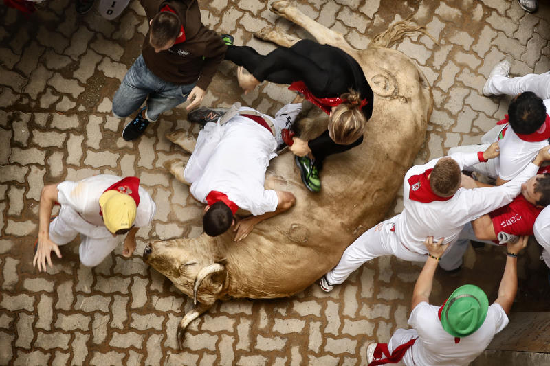 """Revelers run, fall and step over a fallen Fuente Ymbro ranch fighting bull during the running of the bulls of the San Fermin festival, in Pamplona, Spain, Saturday, July 13, 2013. Revelers from around the world arrive to Pamplona every year to take part on some of the eight days of the running of the bulls glorified by Ernest Hemingway's 1926 novel """"The Sun Also Rises."""" (AP Photo/Daniel Ochoa de Olza)"""