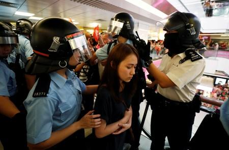 A protester is detained by the police officers at Amoy Plaza shopping mall in Kowloon Bay, Hong Kong