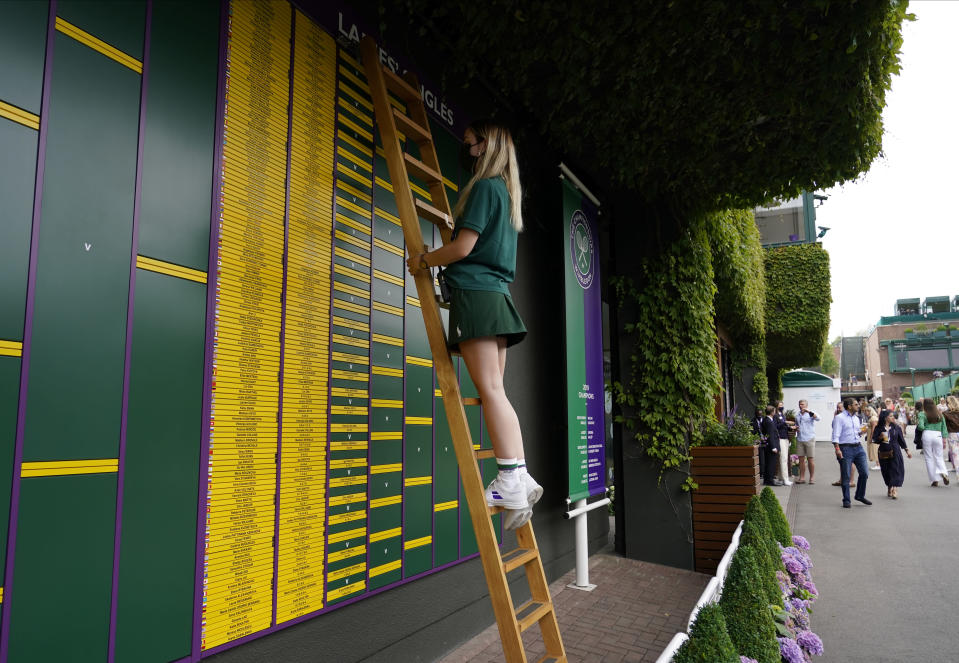 Information is changed to the board in the grounds of the Wimbledon Tennis Championships in London, Thursday July 1, 2021. (AP Photo/Alberto Pezzali)