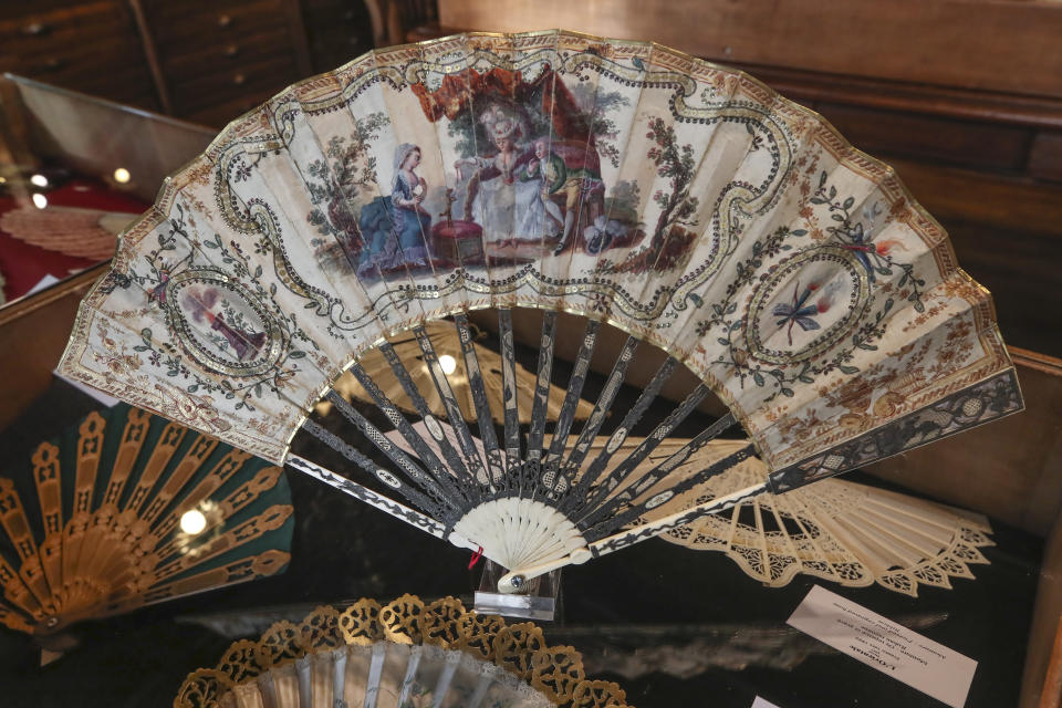A hand fan representing a learned dog (Chien savant), gouache painting on silk dated from 1775, is displayed at the hand fan-making museum in Paris, Wednesday, Jan. 20, 2021. Just like the leaves of its gilded fans, France's storied hand fan-making museum could fold up and vanish. The splendid Musee de l'Eventail in Paris, a classed historical monument, is the culture world's latest coronavirus victim. (AP Photo/Michel Euler)