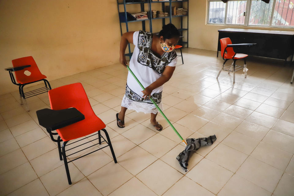 A mother mops the floor of a classroom before the students arrive for their first day of class since the COVID-19 outbreak, at the Valentin Gomez Farias Indigenous Primary School in Montebello, Hecelchakan, Campeche state, Monday, April 19, 2021. Campeche is the first state to transition back to the classroom after a year of remote learning due to the pandemic. (AP Photo/Martin Zetina)