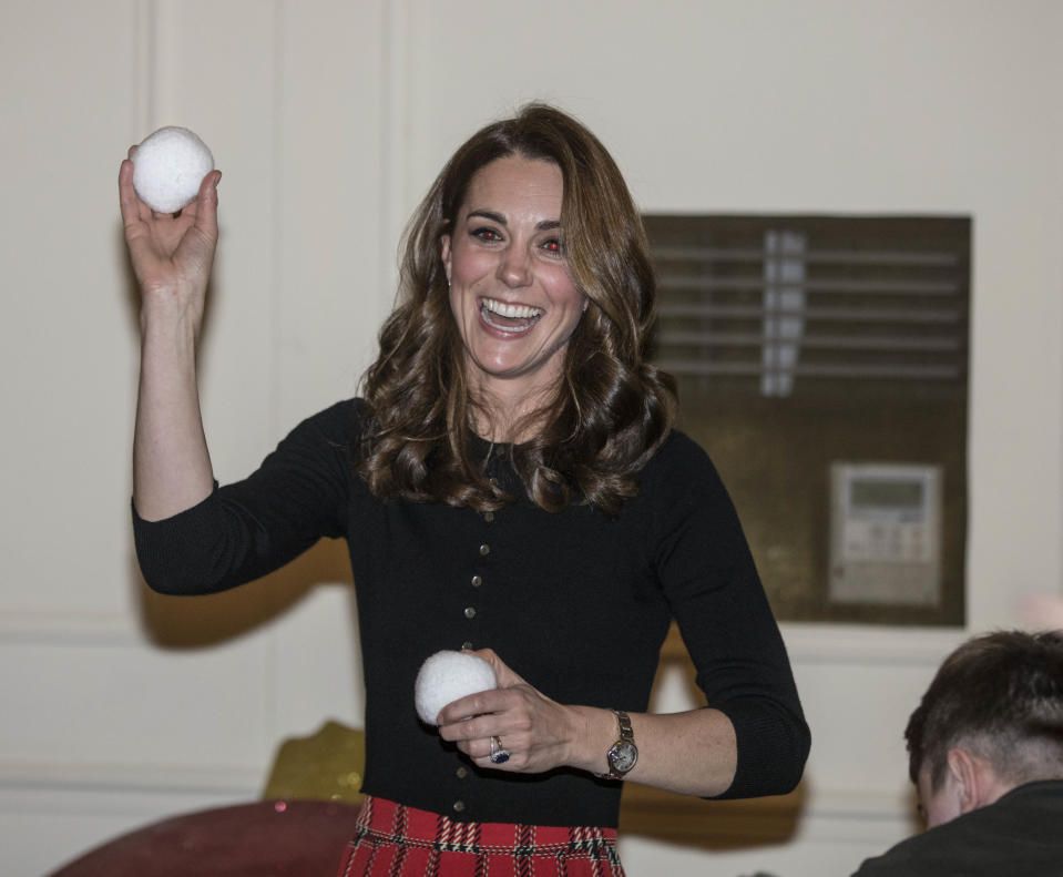 The Duchess of Cambridge throws a mock snowball as she takes part in a children's pretend snowball fight during a Christmas party to deliver a message of support to deployed personnel serving in Cyprus and their families over the festive period in 2018. (Richard Pohle - WPA Pool/Getty Images)
