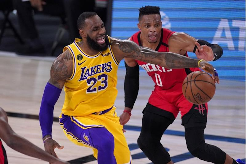 Los Angeles Lakers' LeBron James (23) reaches for the ball as Houston Rockets' Russell Westbrook defends.