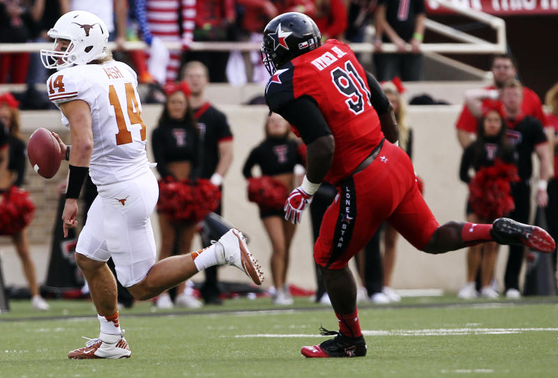 Texas' David Ash runs past Texas Tech's Kerry Hyder during their NCAA college football game, Saturday, Nov. 3, 2012, in Lubbock, Texas. (AP Photo/Lubbock Avalanche-Journal,Stephen Spillman)  LOCAL TV OUT