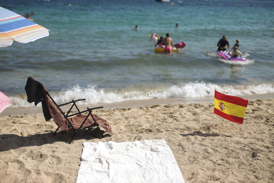A Spanish flag being used as social distancing signage sticks out from the sand in Palma de Mallorca, Spain, Sunday, July 26, 2020. Britain has put Spain back on its unsafe list and announced Saturday that travelers arriving in the U.K. from Spain must now quarantine for 14 days. The move by the UK taken without forewarning has caught travelers off guard. (AP Photo/Joan Mateu)