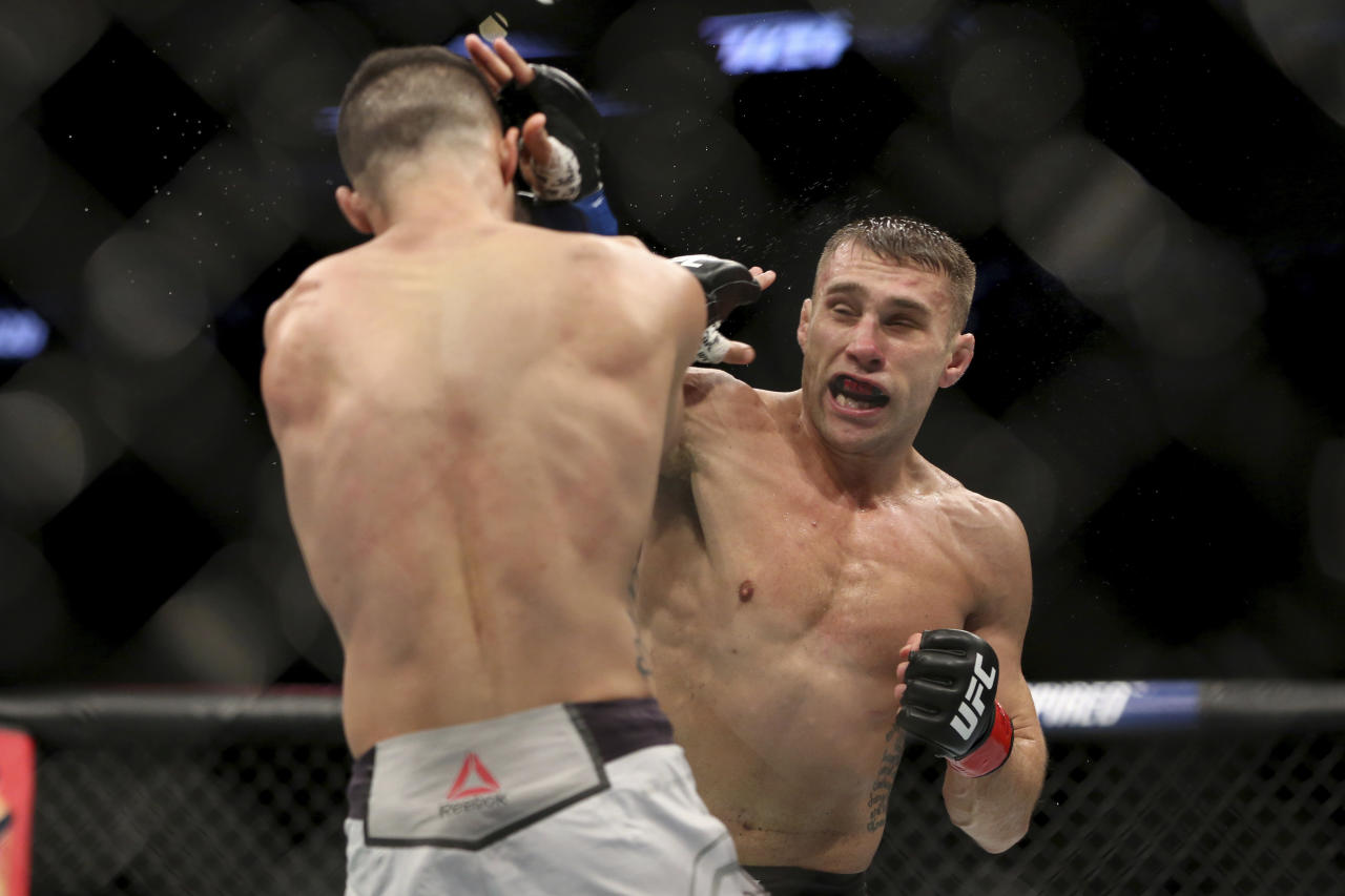 Kyle Bochniak, right, hits Brandon Davis during a mixed martial arts bout at UFC 220, Saturday, Jan. 20, 2018, in Boston. Bochniak won via decision. (AP Photo/Gregory Payan)