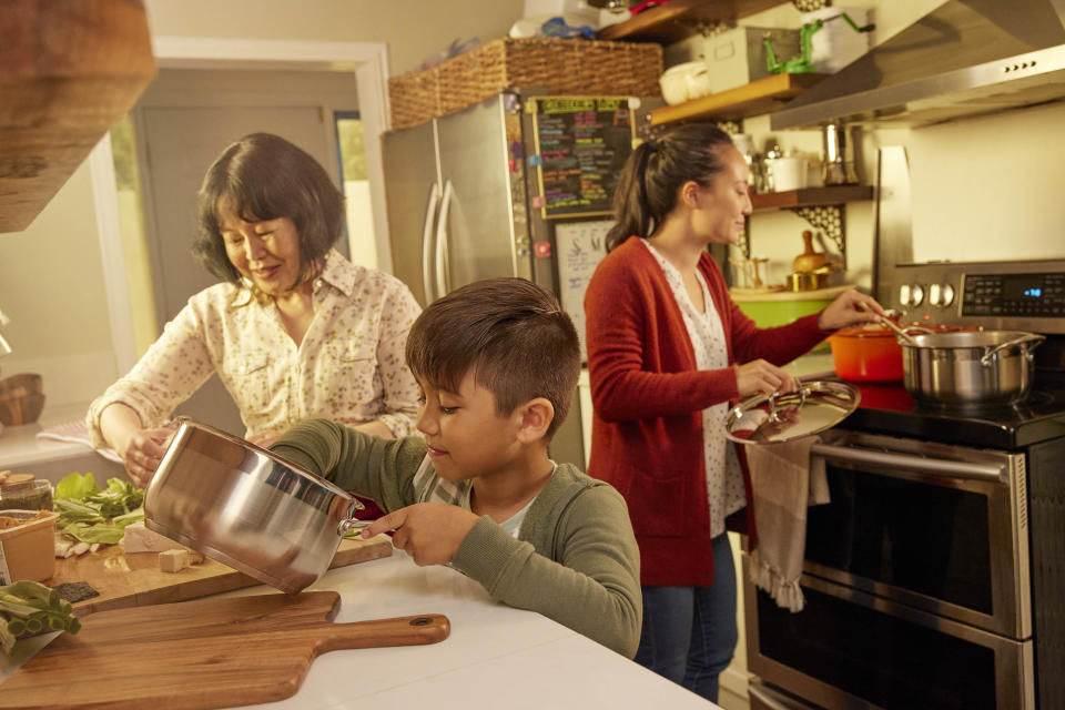 Child helps to prepare lunch with mother and grandmother