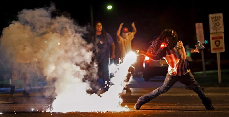 Edward Crawford tosses a tear gas canister fired by police who were trying to disperse protesters in Ferguson, Missouri, on Aug. 13, 2014.  (Photo by Robert Cohen/St. Louis Post-Dispatch)