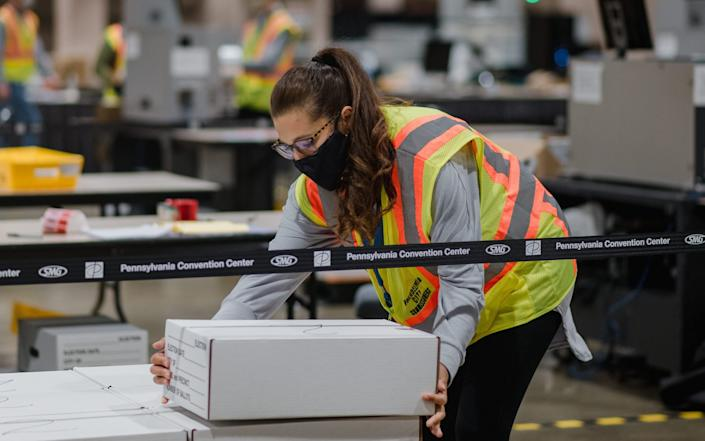 A box of postal ballots arrives in Philadelphia. Pennsylvania is a vital - and hotly-contested - swing state - BLOOMBERG