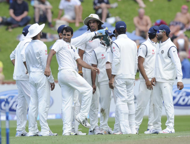 India's Mohammed Shami, center, looks back at the departure of New Zealand's Kane Williamson whose wicket he took for 47 on the first day of the second cricket test in Wellington, New Zealand, Friday, Feb. 14, 2014. (AP Photo/SNPA, Ross Setford) NEW ZEALAND OUT