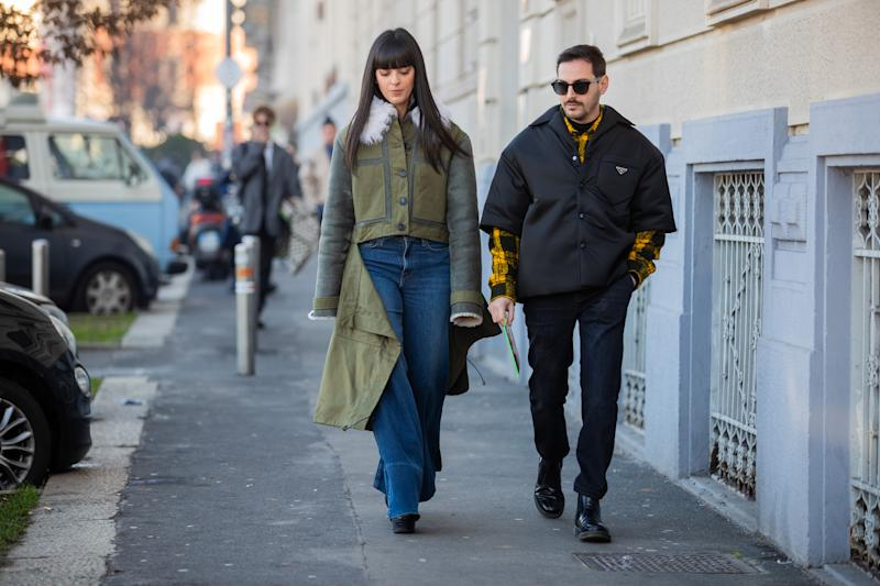 MILAN, ITALY - JANUARY 12: Laura Comolli is seen wearing flared denim jeans, green ripped off coat and Roberto De Rosa wearing Prada jacket outside MSGM during Milan Fashion Week Fall/Winter 2020/2021 on January 12, 2020 in Milan, Italy. (Photo by Christian Vierig/Getty Images)