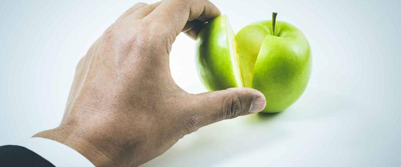 Business market share and success concept.Businessman hand pick a piece of green apple up .
