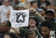 A fan holds up a towel during a parade celebrating the Milwaukee Bucks' NBA Championship Thursday, July 22, 2021, in Milwaukee. (AP Photo/Aaron Gash)