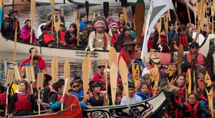 Rocky Mathias-Joe and Gerda Mathias, top centre in headdresses, of the Squamish First Nation, sit on a traditional canoe as paddles are raised on False Creek during an all nations canoe gathering held as part of 2013's Reconciliation Week in Vancouver, B.C. Photo from The Canadian Press