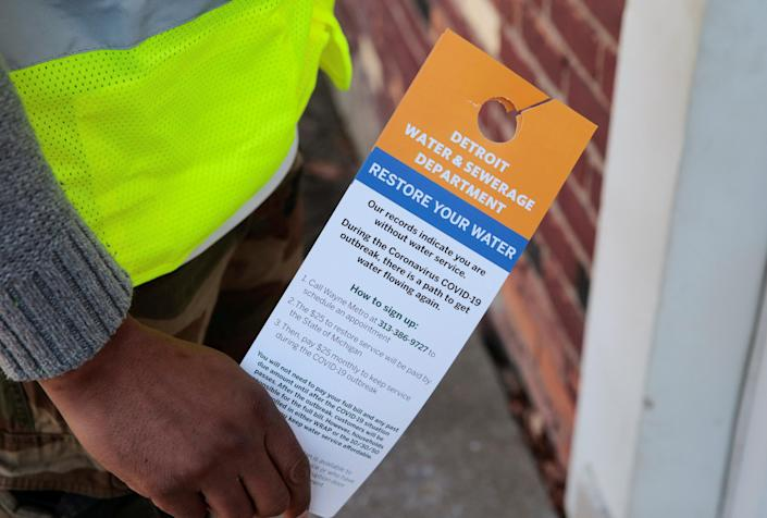 Image: Contract worker Vaughn Harrington holds notices by the Detroit Water and Sewerage Department to inform residents how to restore water service in response to the coronavirus outbreak in Detroit (Rebecca Cook / Reuters)