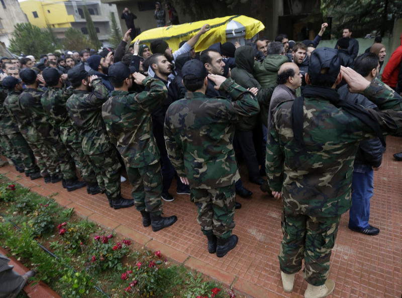 Hezbollah fighters salute as mourners pass by the coffin of Hassan al-Laqis, a senior commander for the Lebanese militant group Hezbollah, who was gunned down, during the funeral procession at his hometown in Baalbek city, east Lebanon, Wednesday, Dec. 4, 2013. The assassination was a major breach of the Shiite militant group's security as it struggles to maintain multiple fronts while it fights alongside President Bashar Assad's forces in Syria. (AP Photo/Hussein Malla)