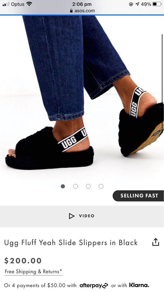 A model wearing Ugg Fluff Yeah Slide Slippers in black on Asos