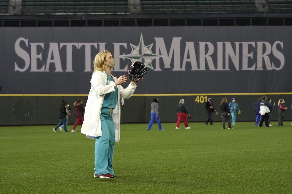 Jessica Sherman, an advanced registered nurse practitioner with Virginia Mason Franciscan Health, plays catch with a colleague in the outfield of T-Mobile Park, the home of the Seattle Mariners baseball team, Monday, March 22, 2021, in Seattle. The Mariners invited health care workers to play catch Monday so they could experience the ballpark ahead of Opening Day on April 1, 2021, and as a way of saying thanks to workers throughout the region who have battled the COVID-19 pandemic in the past year. (AP Photo/Ted S. Warren)