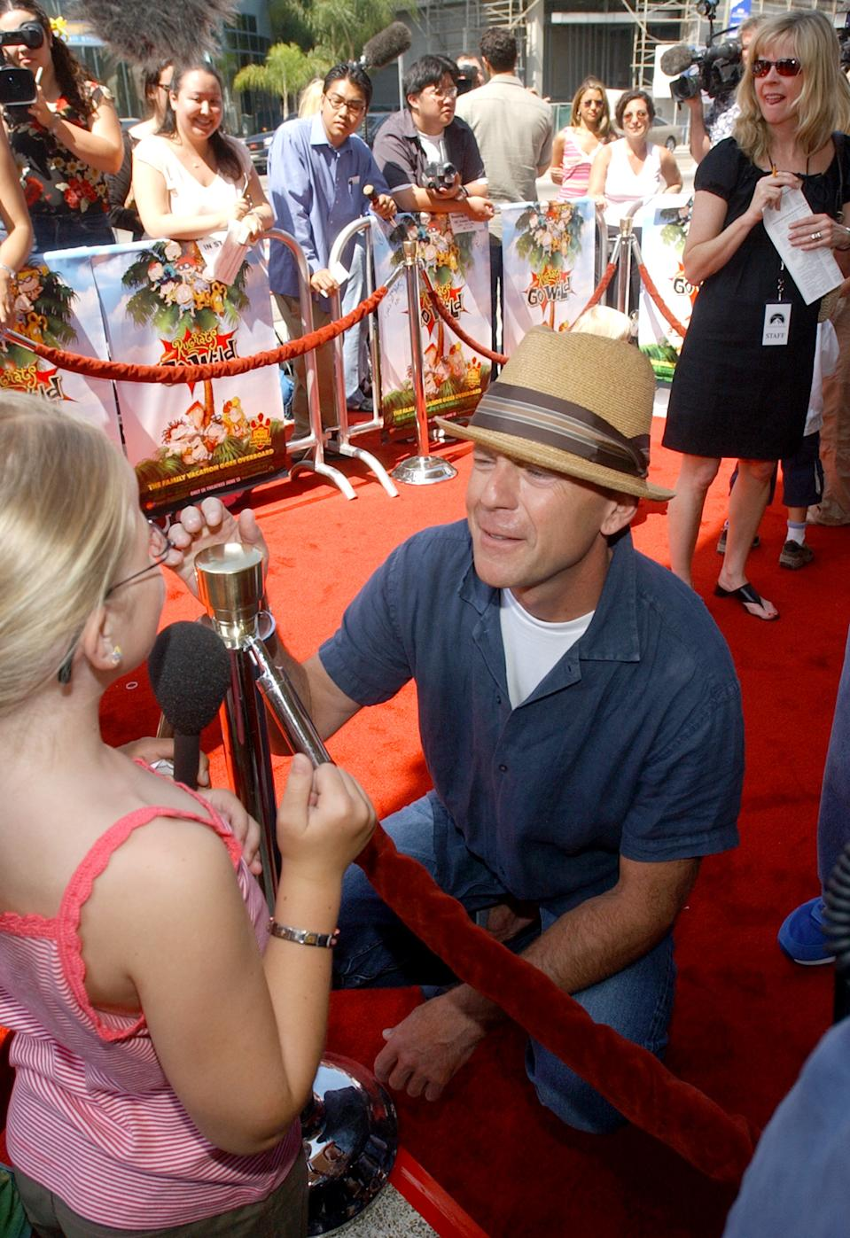 """Actor Bruce Willis, the voice of 'Spike the Dog' in the animated comedy motion picture """"Rugrats Go Wild!"""" is interviewed by seven-year-old Madison Stell of Sacramento, California during the premiere of the film June 1, 2003 in Los Angeles. Willis met Stell yesterday and invited her to attend the premiere. REUTERS/Jim Ruymen JR/GAC"""