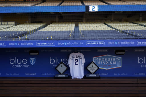 Tommy Lasorda's jersey hangs in the Los Angeles Dodgers' dugout at Dodger Stadium on Friday, Jan. 8, 2021, in Los Angeles. Lasorda, the fiery Hall of Fame manager who guided the Dodgers to two World Series titles and later became an ambassador for the sport he loved during his 71 years with the franchise, died Thursday. He was 93. (AP Photo/Marcio Jose Sanchez)