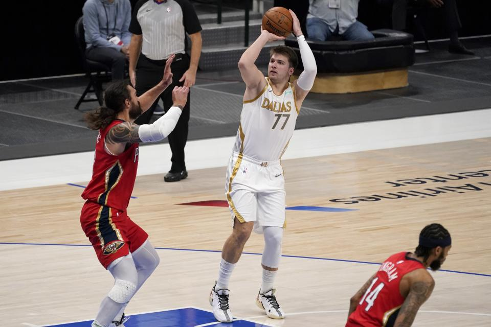 New Orleans Pelicans' Steven Adams, left, defends as Dallas Mavericks' Luka Doncic (77) takes a shot in the first half of an NBA basketball game in Dallas, Friday, Feb. 12, 2021. (AP Photo/Tony Gutierrez)