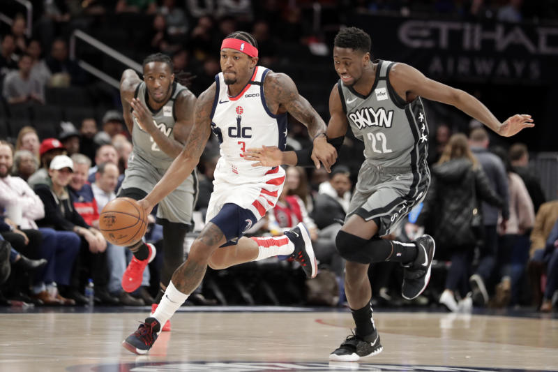 Washington Wizards' Bradley Beal (3) moves the ball as Brooklyn Nets' Taurean Prince (2) and Caris LeVert, right, defend during the first half of an NBA basketball game Wednesday, Feb. 26, 2020, in Washington. (AP Photo/Luis M. Alvarez)