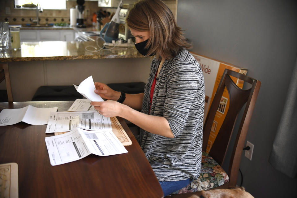 "Melissa Wilhelm Szymanski opens up some of her medical bills at home in Glastonbury, Conn., on Saturday, Sept. 19, 2020. Wilhelm Szymanski got sick earlier this year and wound up with a $3,200 bill because she wasn't diagnosed initially with COVID-19. Even though dozens of insurers and the federal government are offering to pick up all treatment costs during the pandemic, many holes remain for big bills to surprise patients. ""I was surprised that I got a bill because it just so clearly seemed to be COVID,"" said Szymanski. (AP Photo/Jessica Hill)"