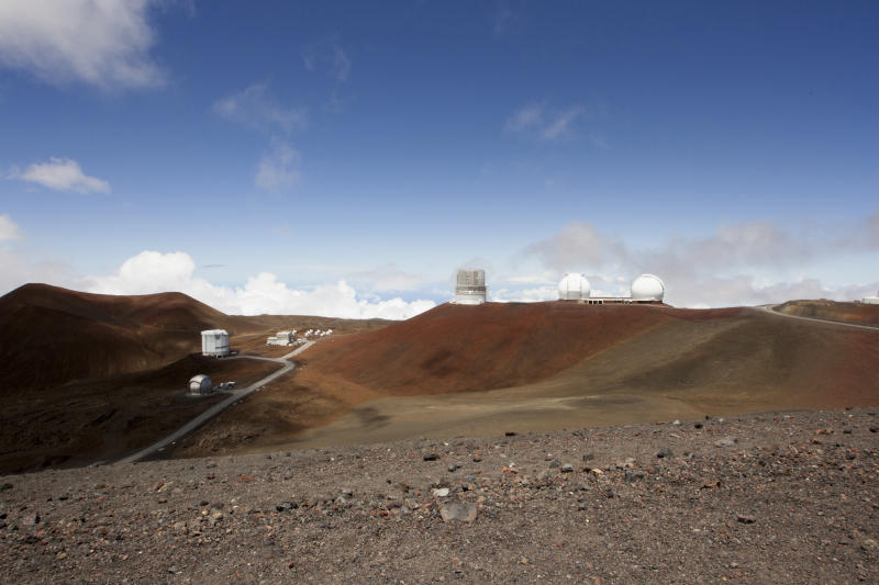 FILE - This Aug. 31, 2015, file photo shows telescopes on the summit of Mauna Kea on Hawaii's Big Island. An agreement has been reached for a giant telescope to be built in Spain's Canary Islands if it cannot be put atop a Hawaii mountain. Telescope builder TMT International Observatory says Hawaii's Mauna Kea remains the preferred location for the $1.4 billion Thirty Meter Telescope. (AP Photo/Caleb Jones, File)