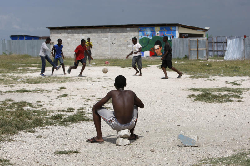 In this May 17, 2012 photo, a youth watches others play soccer in the Cite Soleil shantytown at the site where a stadium may be built in Port-au-Prince, Haiti. A local sports hero, a New York real estate developer and a well-known architect are teaming up to build a soccer stadium here, hoping to revive the seaside shantytown. The organizers also hope the stadium, scheduled to break ground within six months and due to be built by the end of 2013, will bring an initial 500 jobs and inject commerce into the shanty city, where politicians to pay residents to fight their battles as proxy forces. (AP Photo/Dieu Nalio Chery)