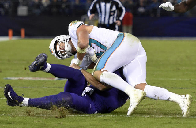 Miami Dolphins middle linebacker Kiko Alonso, top, collides with Baltimore Ravens quarterback Joe Flacco as Flacco slides on the field after rushing the ball in the first half. (AP)