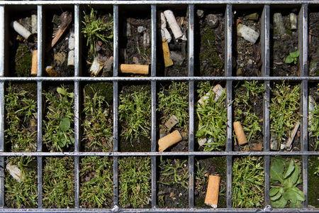 Cigarette butts are seen in a metal grate on a street in Lyon, France, June 14, 2018. The French government wants to end the bane of discarded cigarette butts and will impose new regulations unless tobacco companies come up with proposals to reduce their number. REUTERS/Emmanuel Foudrot