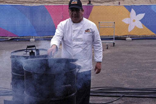 """In this Aug. 8, 2019 photo, chef Edwin Guzman of the Estilo y Sabor catering house poses for photos cocking """"chancho al cilindro"""", or pork roasted in an oil drum at the international center outside the Pan American athletes' village in Lima, Peru. Peruvian food was the star at the recent Pan Am Games held in Latin Americas culinary capital. Athletes from countries across the Americas tasted the highly-regarded cuisine that blends indigenous traditions with European, African and Asian influences with an abundance of seafood from the Pacific Oceans cold Humboldt current. (AP Photo/Luis Andres Henao)"""