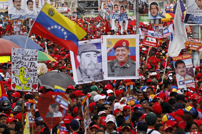 Holing images of Venezuela's late President Hugo Chavez, right, and Cuba's Fidel Castro, left, supporters attend the closing campaign rally for Venezuela's acting President Nicolas Maduro in Caracas, Venezuela, Thursday, April 11, 2013. Maduro, the hand-picked successor of Chavez, is running for president against opposition candidate Henrique Capriles on April 14. (AP Photo/Ariana Cubillos)