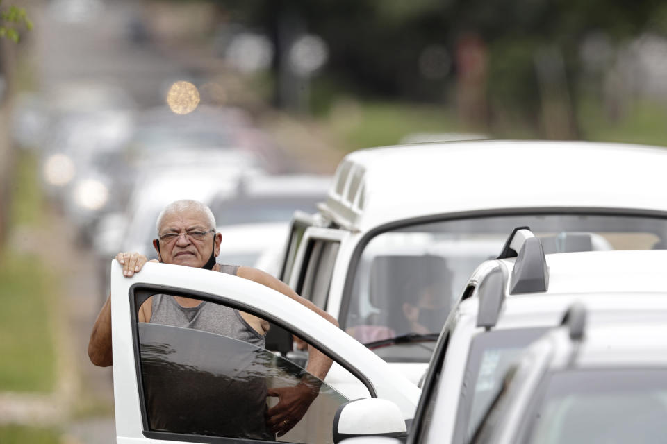 FILE - In this March 22, 2021 file photo, a man stands next to his vehicle in a line at a COVID-19 vaccination point for priority elderly persons in the Ceilandia neighborhood, on the outskirts of Brasilia, Brazil. As Brazil hurtles toward an official COVID-19 death toll of 500,000, its Senate is publicly investigating how the pandemic death toll got so high, focusing on why the government ignored opportunities to buy vaccines while pushing hydroxychloroquine. (AP Photo/Eraldo Peres, File)