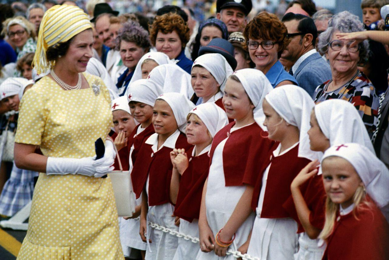 <p>Young schoolgirls in Brisbane greet The Queen during her Silver Jubilee tour of Australia. She celebrated the 25th anniversary of her accession to the throne this year. (PA Archive) </p>