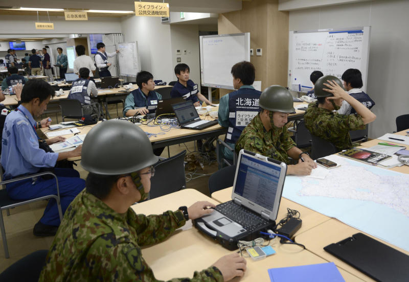 Members of disaster countermeasures office work at Hokkaido Government in Sapporo, northern Japan Thursday, Sept. 6, 2018. A powerful earthquake struck the island of Hokkaido early Thursday. (Kyodo News via AP)