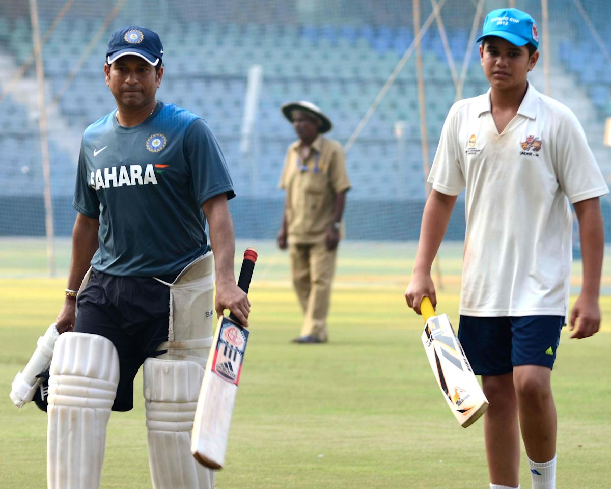 Indian cricketer Sachin Tendulkar with his son arjun Tendulkar during practice session ahead of his 200th and the last Test match at Wankhede stadium in Mumbai on Nov.12, 2013. (Photo: Sandeep Mahankaal/IANS)