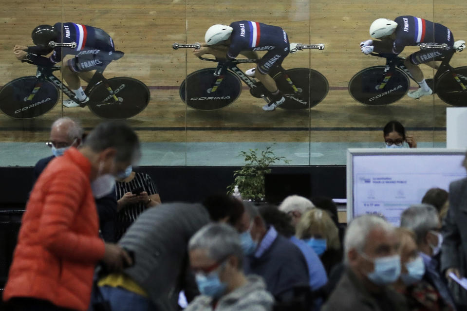 Riders of the French cycling team train as people wait for their vaccine shot at the National Velodrome that has been transformed into a mass vaccination center in Saint-Quentin-en-Yvelines, west of Paris, Monday, March 29, 2021. (AP Photo/Christophe Ena)
